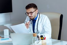Confident male doctor writing information of his patient in the office. Portrait of confident male doctor writing information of his patient in the office Stock Images