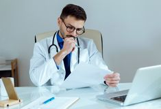 Confident male doctor writing information of his patient in the office. Portrait of confident male doctor writing information of his patient in the office Stock Photos