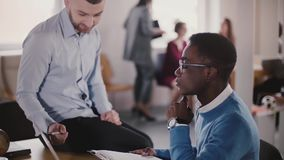 Confident male executive is helping his African American young colleague in modern light coworking, slow motion close-up