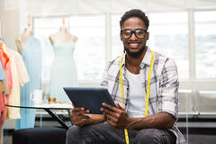 Confident male fashion designer with digital tablet. Portrait of smiling confident male fashion designer with digital tablet Royalty Free Stock Photo