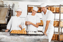 Confident Male And Female Baker's Standing At Table Royalty Free Stock Images