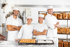 Confident Male And Female Baker's Standing At Table Stock Photography