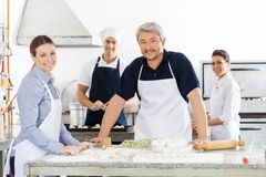 Confident Male And Female Chefs Preparing Pasta At Stock Photography