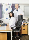 Confident Male And Female Doctors At Desk In Clinic Stock Image