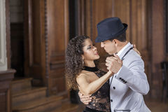 Confident Male And Female Partners Performing Tango. Side view of confident male and female partners performing tango in restaurant Stock Images