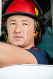 Confident Male Firefighter Sitting In Firetruck Stock Photos