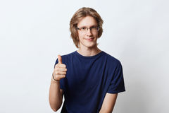 Confident male freelancer with stylish hairdo, wearing spectacles, showing ok sign while raising his thumb, agreeing with somethin Royalty Free Stock Image