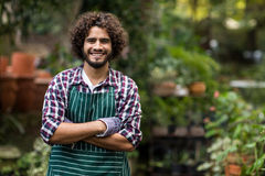 Confident male gardener standing at greenhouse. Portrait of confident male gardener standing with arms crossed at greenhouse Royalty Free Stock Images