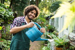 Confident male gardener watering potted plants Stock Images