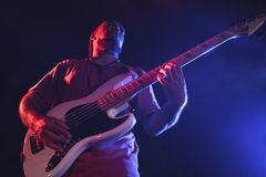 Confident male guitarist performing at concert. Low angle view of confident male guitarist performing at concert Stock Image
