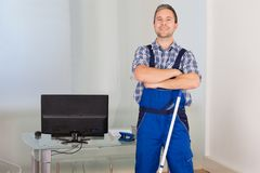 Confident male janitor. Portrait Of Happy Confident Male Janitor With Mop In Office Royalty Free Stock Photos