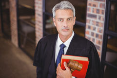 Confident male lawyer with gavel and red book Royalty Free Stock Photos