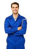 Confident Male Mechanic Holding Wrench. Portrait of confident male mechanic standing with arms crossed holding wrench over white background. Vertical shot Royalty Free Stock Image