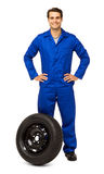 Confident Male Mechanic With Spare Tire Royalty Free Stock Photography
