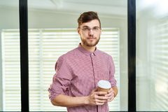 Confident male office worker. Waist-up portrait of young bearded Caucasian man in glasses and checked shirt holding coffee to-go and looking at camera Royalty Free Stock Photo