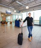 Confident Male Passenger With Luggage At Airport Terminal Stock Image