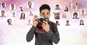 Confident male photographer holding camera against flying portraits. Digital composite of Confident male photographer holding camera against flying portraits Royalty Free Stock Images