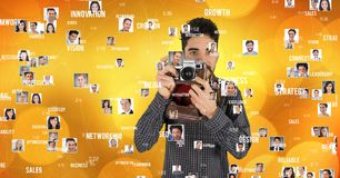 Confident male photographer holding camera surrounded with flying portraits Royalty Free Stock Images
