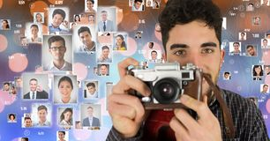 Confident male photographer holding camera surrounded by flying portraits over bokeh Stock Images
