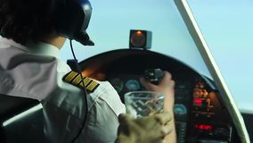 Confident male pilot operating airplane and refusing alcoholic drink in cockpit