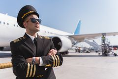 Confident male pilot standing outside. Serious aviator wearing sunglasses is locating afore big aircraft. He looking up with confidence. Copy space on right side Stock Images
