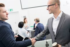 Professionals Shaking Hands In Seminar Hall. Confident male professionals shaking hands in seminar hall Royalty Free Stock Photos