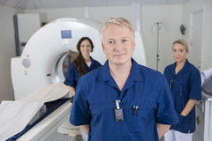 Confident Male Radiologist With Colleagues Standing By MRI Machi Stock Image