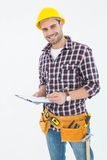 Confident male repairman writing on clipboard. Portrait of confident male repairman writing on clipboard over white background Royalty Free Stock Photography
