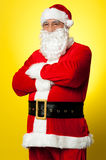 Confident male Santa posing with arms folded. Isolated over yellow background Royalty Free Stock Images