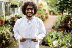 Confident male scientist holding digital tablet. Portrait of confident male scientist holding digital tablet at greenhouse Royalty Free Stock Images