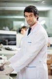 Confident Male Scientist. Portrait of confident male scientist in laboratory working centrifuge Stock Photo