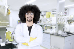 Confident male scientist. In protective glasses and lab coat standing with crossed arms and looking at camera in the lab Stock Photo