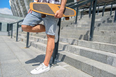Confident male skateboarder relaxing on steps. Close up of legs of young man is standing on staircase and leaning leg on border. He is holding skate Royalty Free Stock Photography