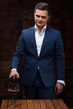 Confident male sommelier pouring wine to wineglass. A sommelier pouring red wine into wineglass. Sommelier at work. Confident male sommelier pouring wine to Stock Image