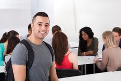 Confident Male Student Carrying Backpack In Classroom Royalty Free Stock Images