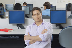 Confident Male Student In Computer Lab. Portrait of a confident male student in computer lab with classmates in the background Stock Images