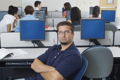 Confident Male Student In Computer Lab. Portrait of a confident male student in computer lab with classmates in the background Royalty Free Stock Photo