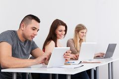 Confident Male Student Holding Digital Tablet At Desk Royalty Free Stock Image