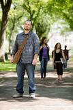 Confident Male Student On Standing Campus Road. Full length portrait of confident male student standing on campus road with friends in background Royalty Free Stock Photo