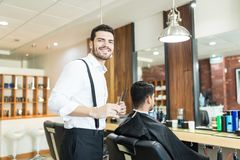Stylist Smiling While Grooming Client`s Hair In Barber Shop stock photography