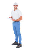 Confident male supervisor writing on clipboard over white background. Full length portrait of confident male supervisor writing on clipboard over white Royalty Free Stock Photography