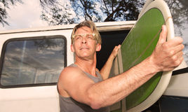 Confident Male Surfer. Holding his surfboard near van Stock Photo