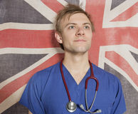 Confident male surgeon looking up with British Flag in background Royalty Free Stock Photos