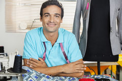 Confident Male Tailor Leaning On Workbench By Mannequin Stock Images