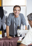 Confident Male Tailor Leaning On Workbench Stock Photography
