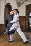 Confident Male Tango Dancers Performing Gancho. Full length of confident male tango dancers performing gancho in restaurant Stock Image