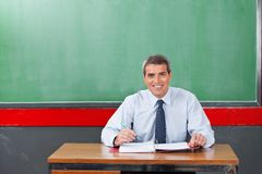 Confident Male Teacher With Pen And Binder Sitting. Portrait of confident mature male teacher sitting with binder and pen at desk in classroom Stock Photos