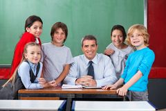 Confident Male Teacher With Schoolchildren At Desk. Portrait of happy confident mature male teacher with schoolchildren together at desk in classroom Stock Photo