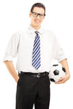 Confident male with tie holding a football Stock Photo