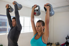 Confident male trainer with athlete lifting kettlebells. In gym Stock Images